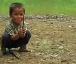 A boy playing with a butterfly tied to the end of a stick