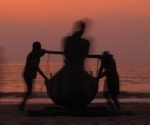 Fishermen drag their boat up the Gokarna's beach