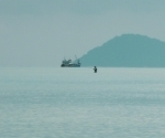 A fisherman wades in shallow water a few hundred metres out