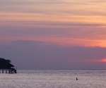 A fisherman wades off Koh Mak's northern beach at sunset