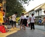 Children playing hopscotch on Kingkitsarath Road