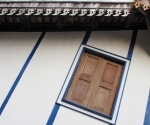 Skirting like hooked daggers on a wooden home painted blue and white