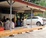 A monk performing a baci to bless a car at Wat Simuang