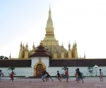 Boys playing soccer behind Pha That Luang