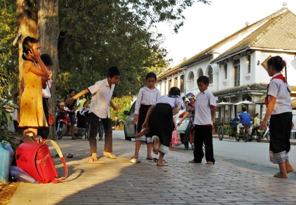 Children playing hopscotch on Kingkitsarath Road