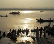 Bathers in dawn's golden light, reflected on the Ganges