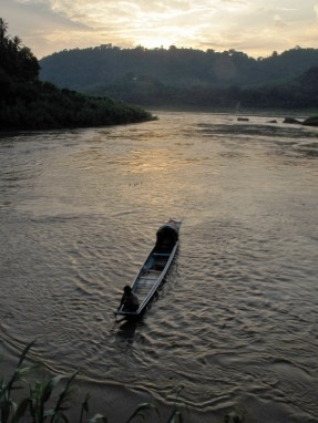 A riverboat with a sun shelter on the Nam Khan in the day's last light