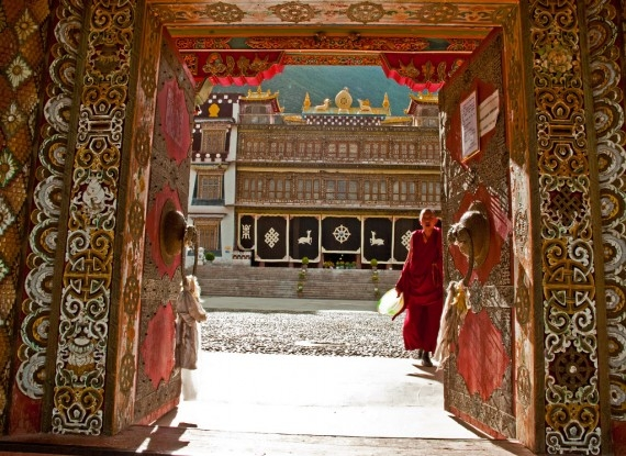 A monk at the entrance to Bsampeling Monastery in Xiangcheng