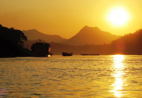 River boats slip across an orange Mekong